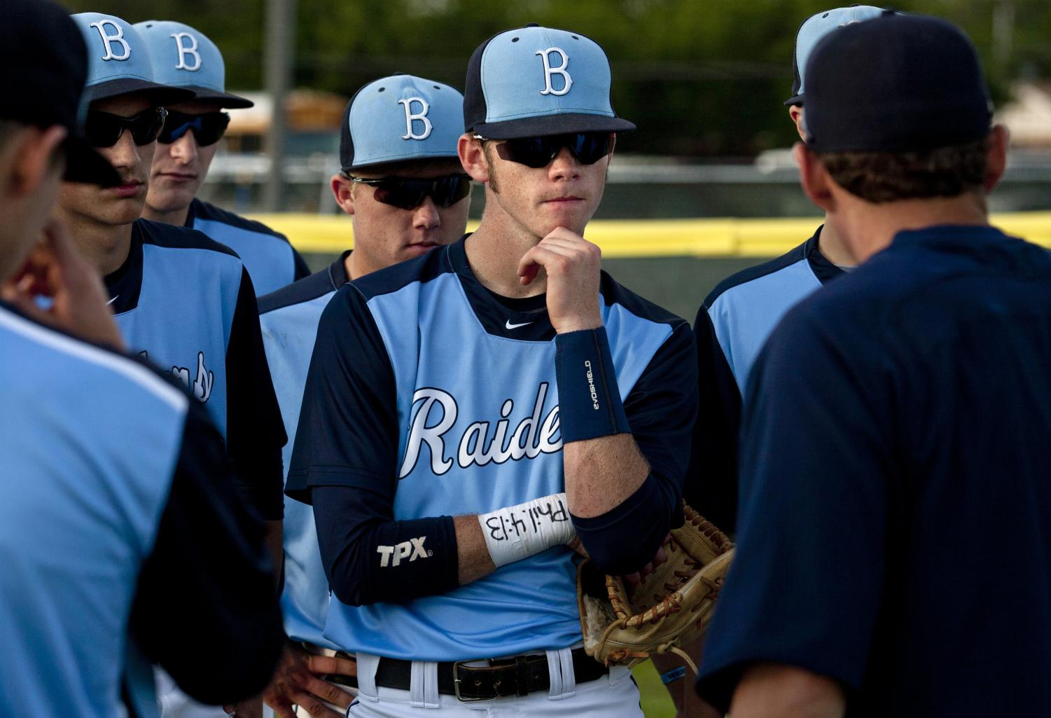 High School baseball coach has a meeting at the mound with his pitcher, and infielders.