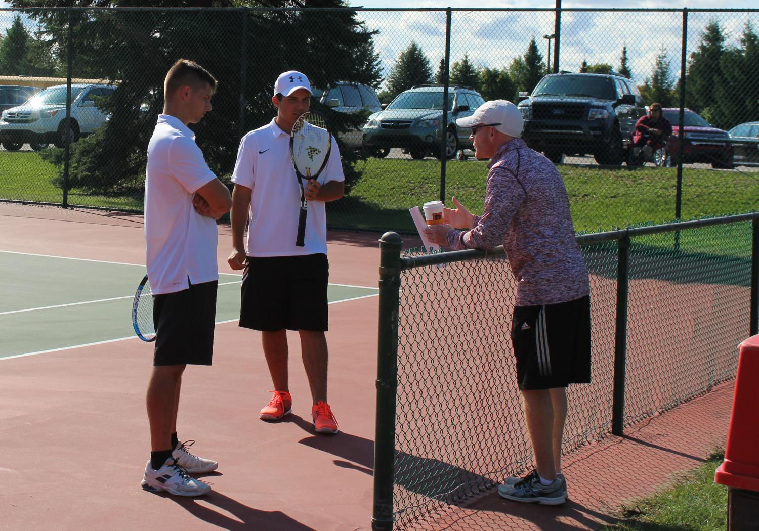Coach Stephen Nellis does some last minute coaching to help senior Zachary Yurconis and junior Jacob Giardina prepare for their upcoming match.