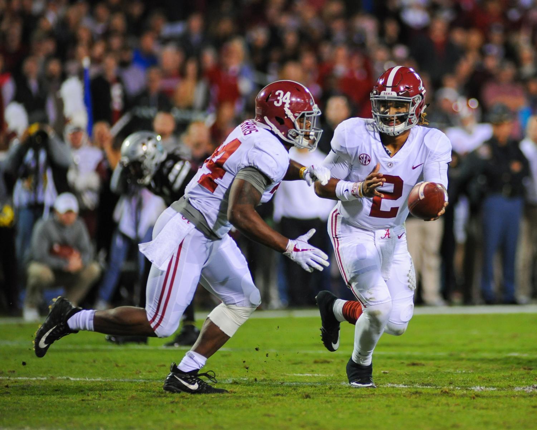 Alabama Crimson Tide quarterback Jalen Hurts (2) hands the ball off to running back Damien Harris (34) against Mississippi State.