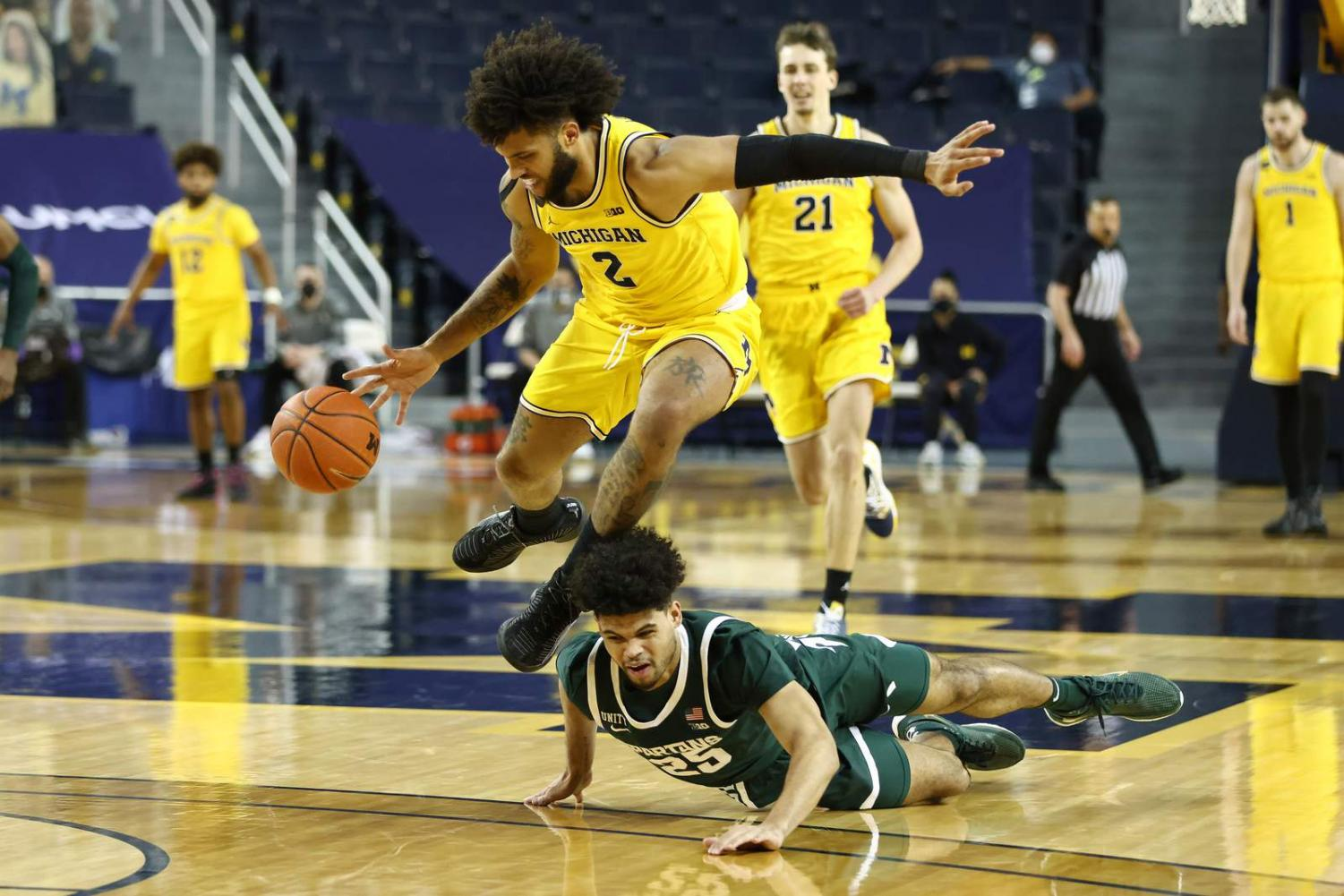 Isaiah Livers of the Michigan Wolverines pursues a loose ball against Malik Hall of the Michigan State Spartans.